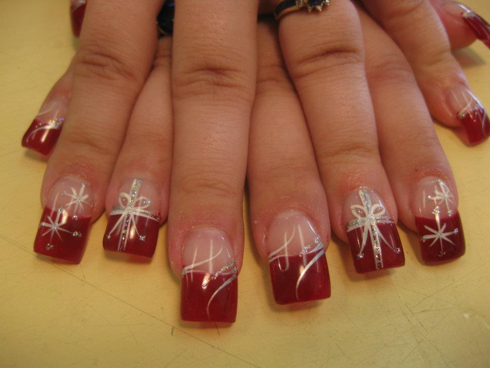 christmas red tip topped by flesh colored nail with whitesparkling christmas present bow and
